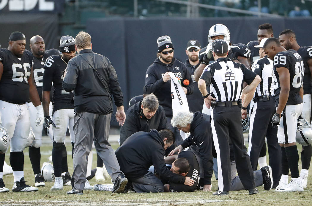 Oakland Raiders quarterback Derek Carr, bottom, is tended to after being injured against the In ...