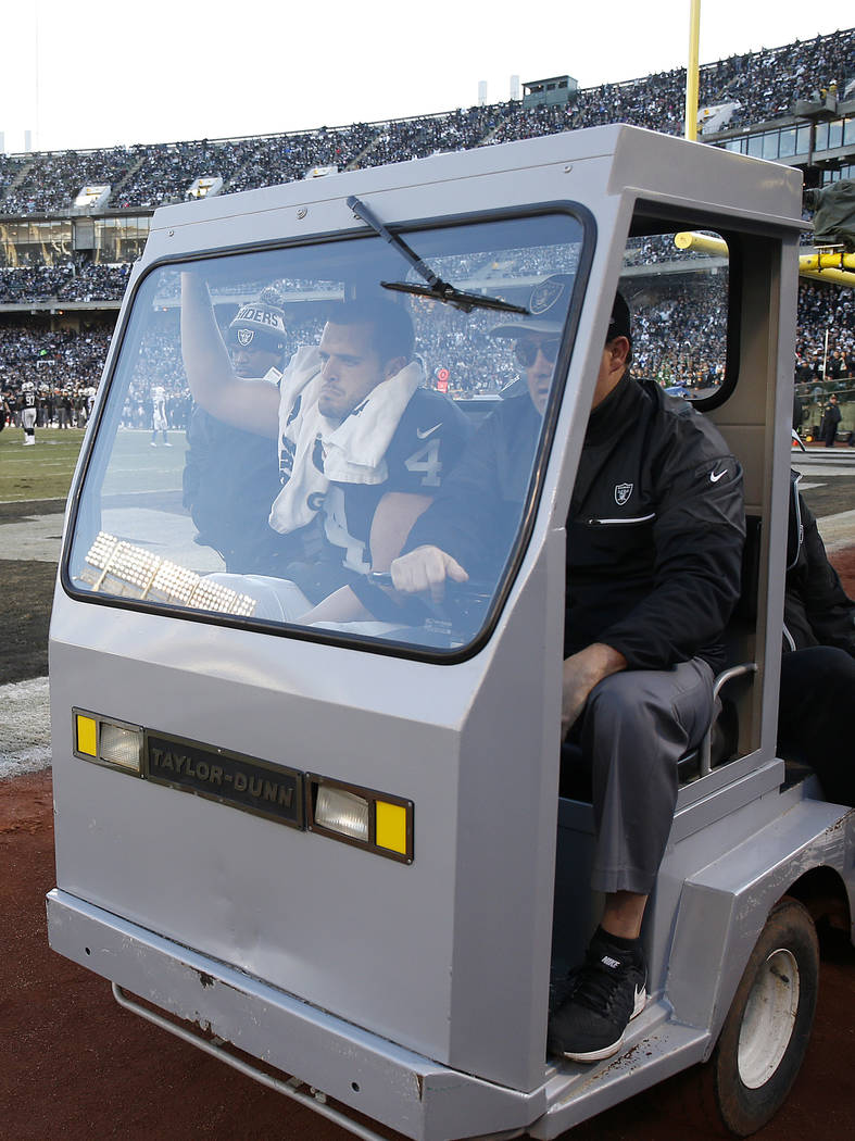 Oakland Raiders quarterback Derek Carr, left, is carted off the field after being injured again ...