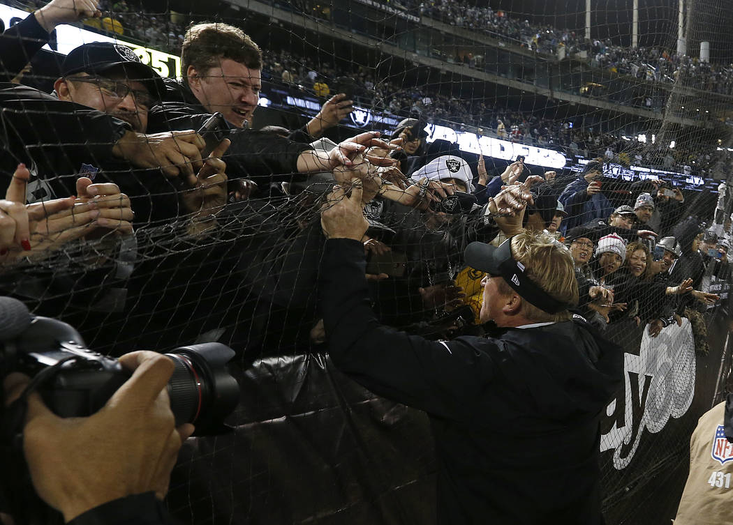 Oakland Raiders head coach Jon Gruden, bottom right, greets fans after an NFL football game aga ...