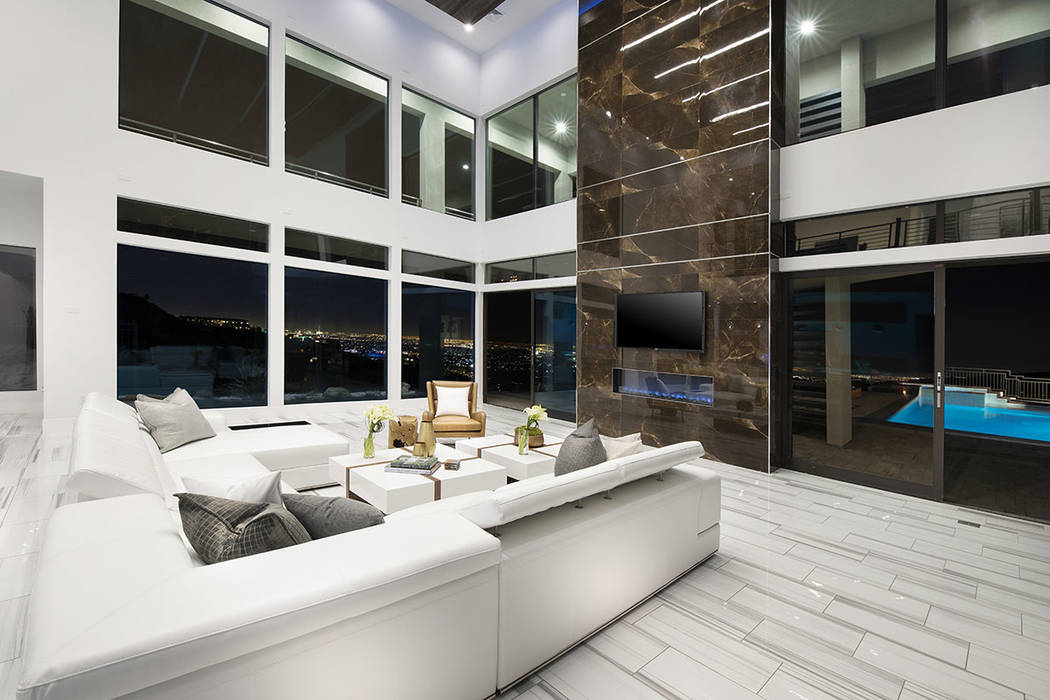 The living room features floor-to-ceiling windows and a fireplace. (Synergy Sotheby's Interna ...