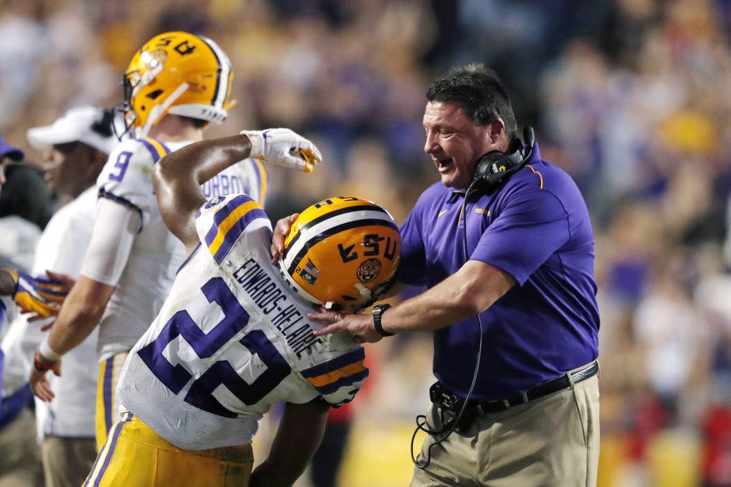 LSU coach Ed Orgeron celebrates with running back Clyde Edwards-Helaire (22) after a touchdown ...