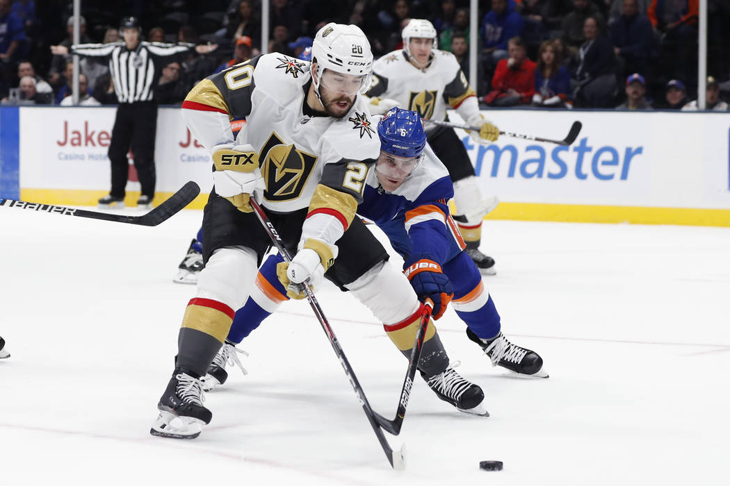 Vegas Golden Knights center Chandler Stephenson (20) tries to steer the puck away from New York ...