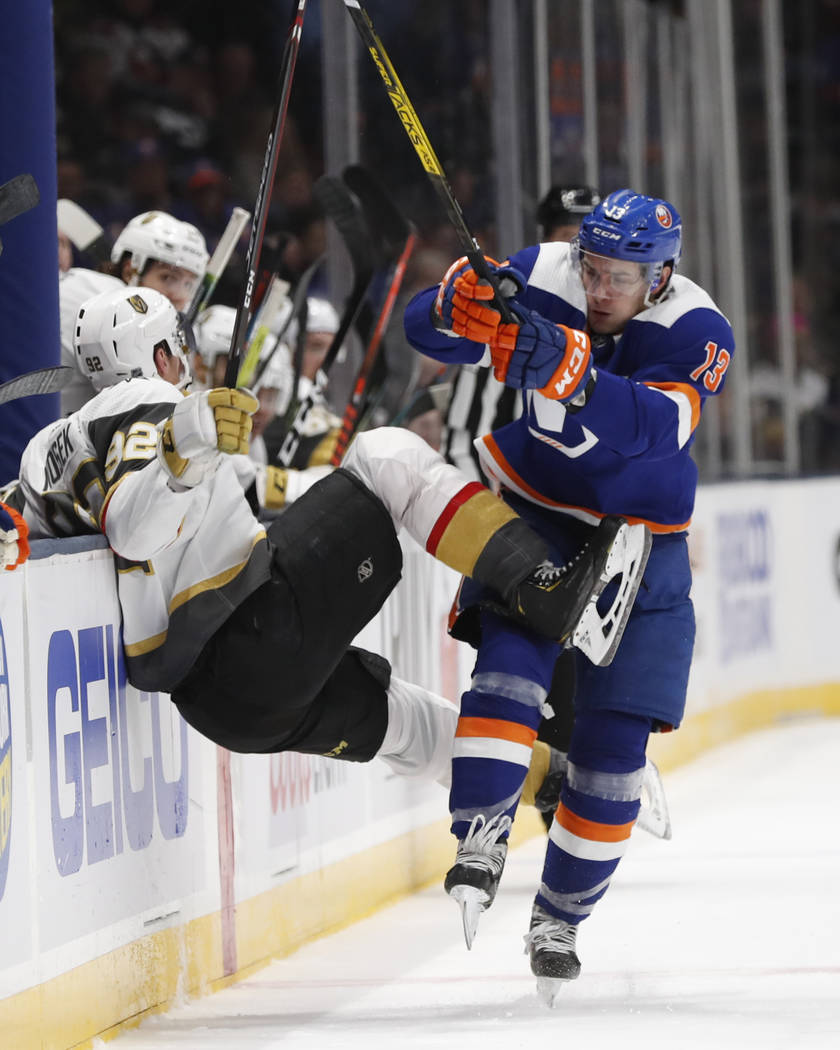 New York Islanders center Mathew Barzal (13) collides with Vegas Golden Knights left wing Tomas ...