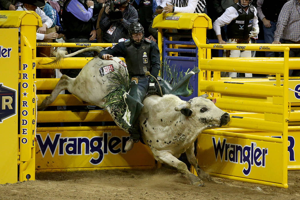 Jordan Hansen of Canada rides Hou's Bad News to a score of 89.5 in the Bull Riding competition ...