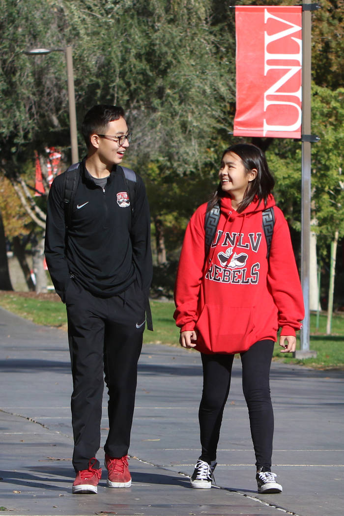 Shenlone Wu, 12, and his sister Shenmei, 13, both full-time students at UNLV, walk along a side ...