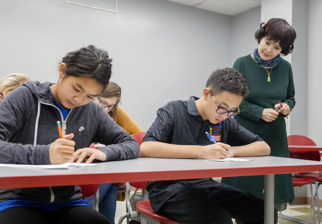 UNLV students Shenmei Wu, 13, left, and Shenlone Wu, 12, center, and professor Xiaoling Hays fo ...