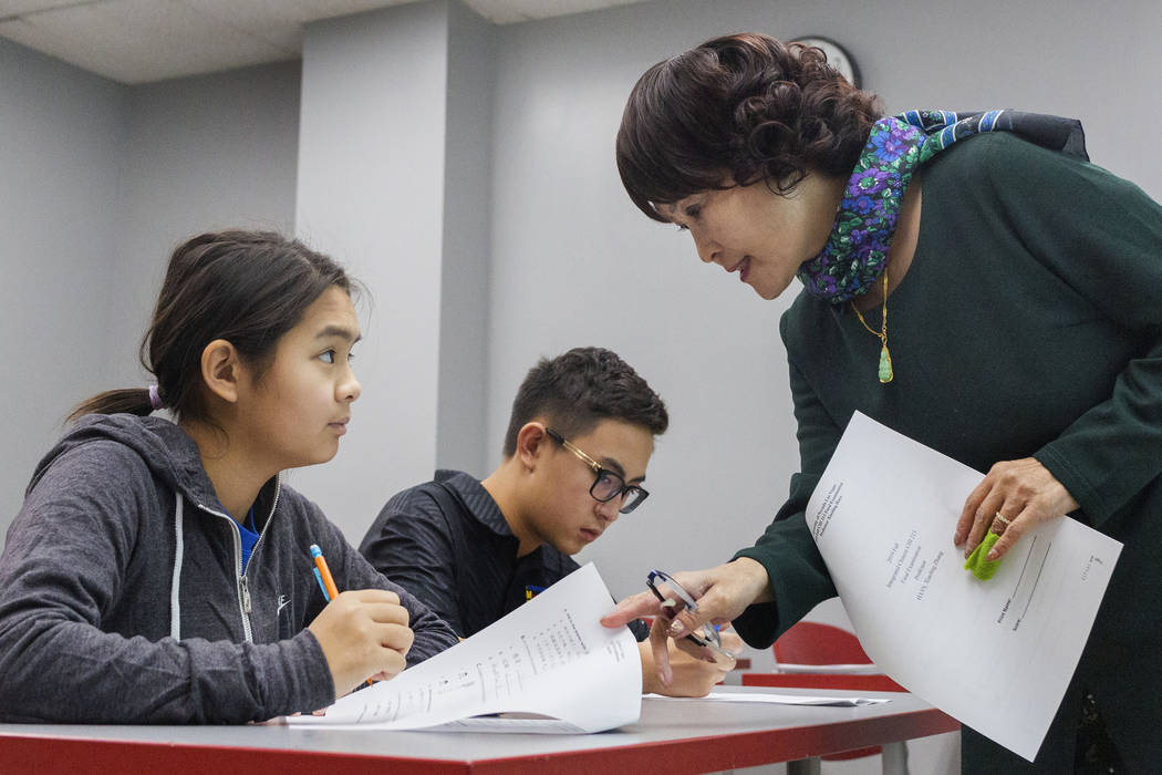 Shenmei Wu, 13, left, listens to UNLV Chinese professor Xiaoling Hays, next to her brother Shen ...
