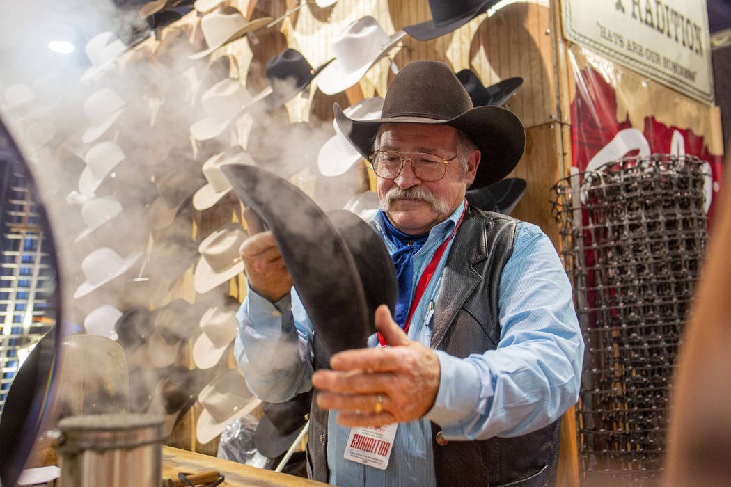 Owner of Western Tradition Rick Bishop cleans and reshapes a hat during Cowboy Christmas at the ...