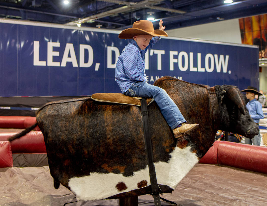 Riggin Osborne, 5, of Mountain View, Wyo., rides a mechanical bull at Cowboy Christmas at the L ...