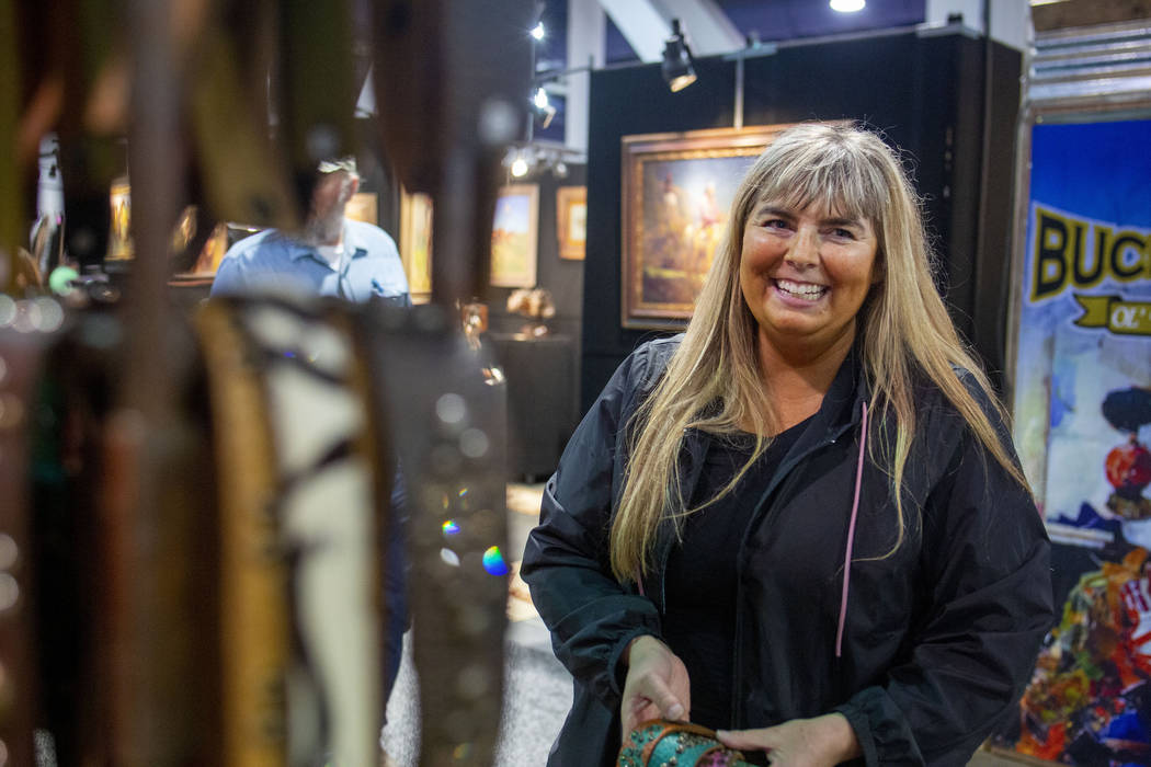 Owner of McFadin Leather Goods Laurie McFadin of Sabinal, Texas, hangs handmade leather straps ...