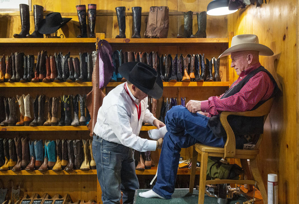 M.L. Leddy's boot measurer Gabe Martinez of Fort Worth, Texas, left, prepares for custom made b ...
