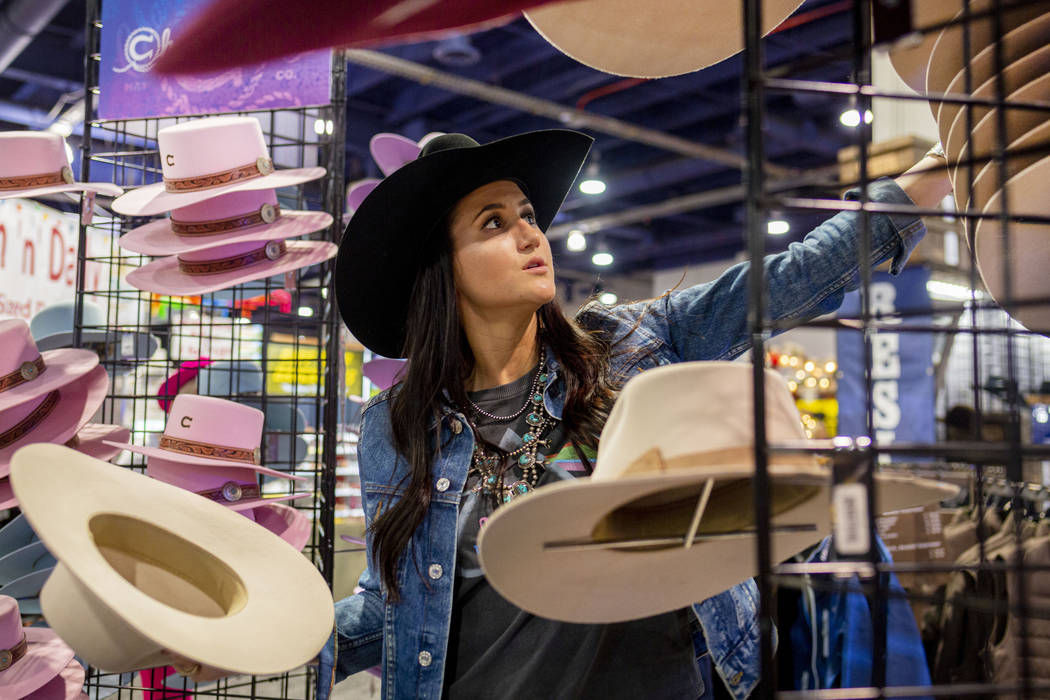 Kylee Hamilton of Texas, marketing for Charlie 1 Horse, organizes felt hats available for purch ...