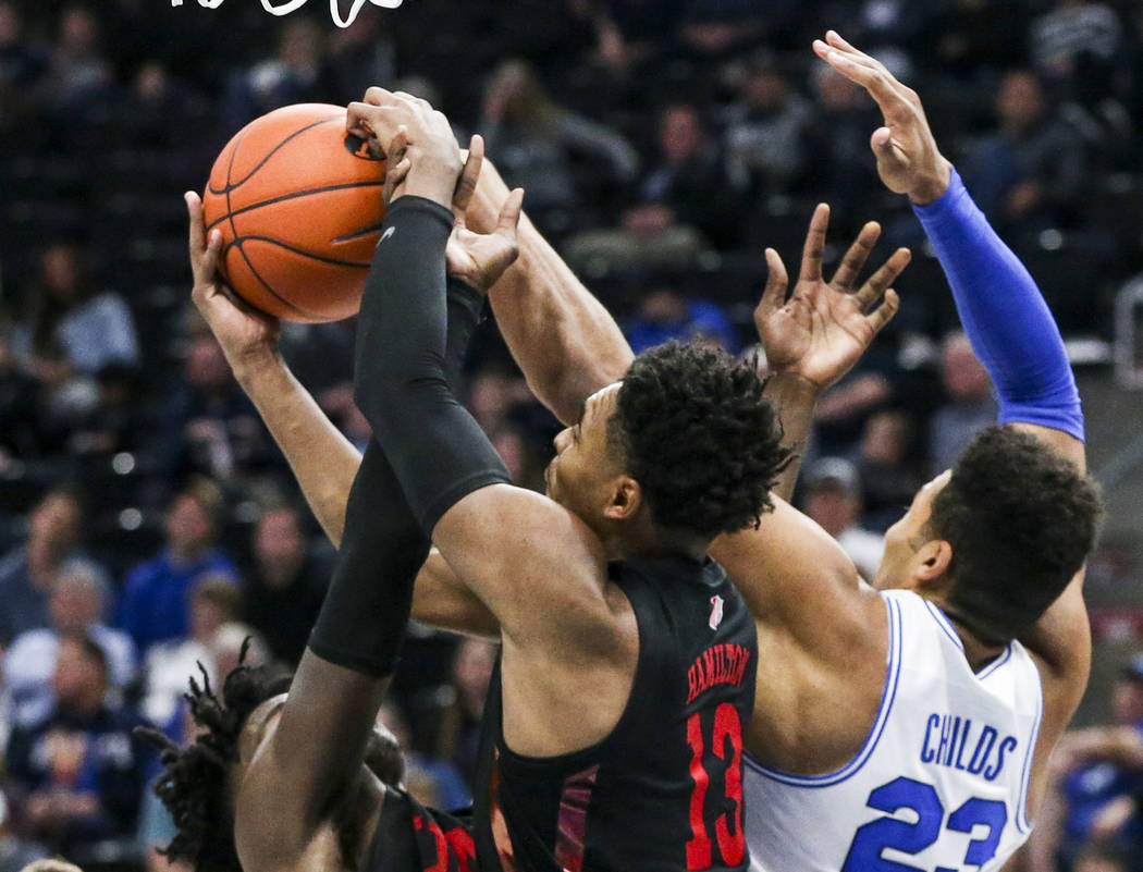 UNLV guard Bryce Hamilton (13) comes down with a rebound against BYU forward Yoeli Childs (23) ...