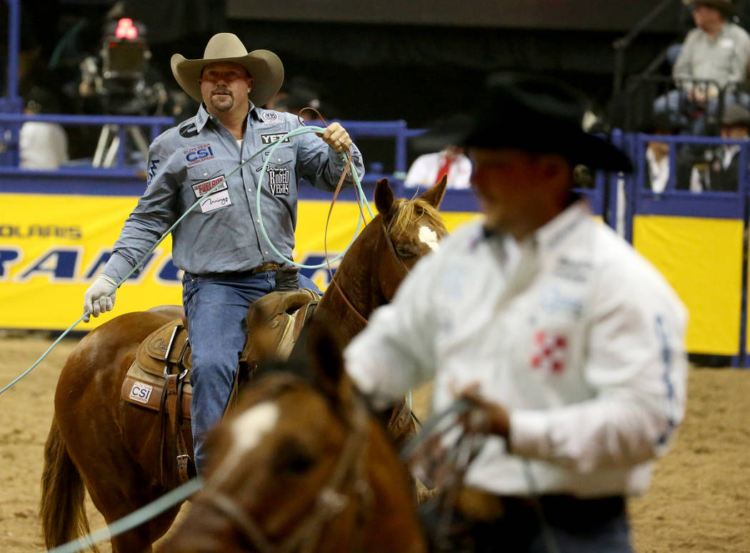 Kyle Lockett of Visalia, Calif., left, after competiting in Team Roping with Erich Rogers of Ro ...