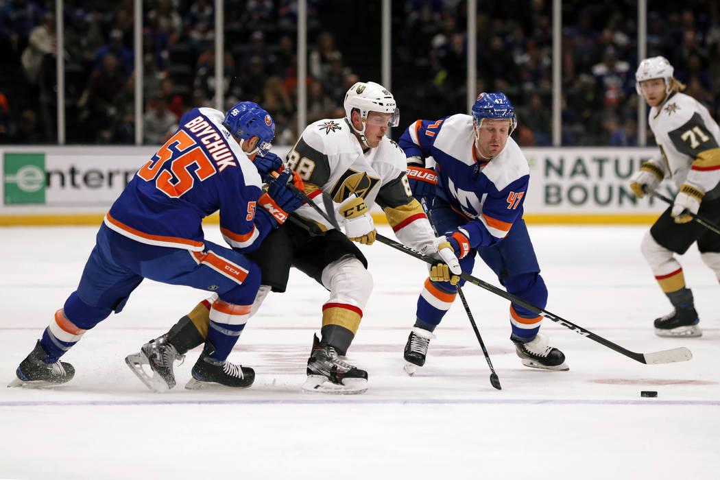 New York Islanders defenseman Johnny Boychuk (55) and right wing Leo Komarov (47) surround Vega ...