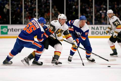 New York Islanders defenseman Johnny Boychuk (55) and right wing Leo Komarov (47) surround Vega ...