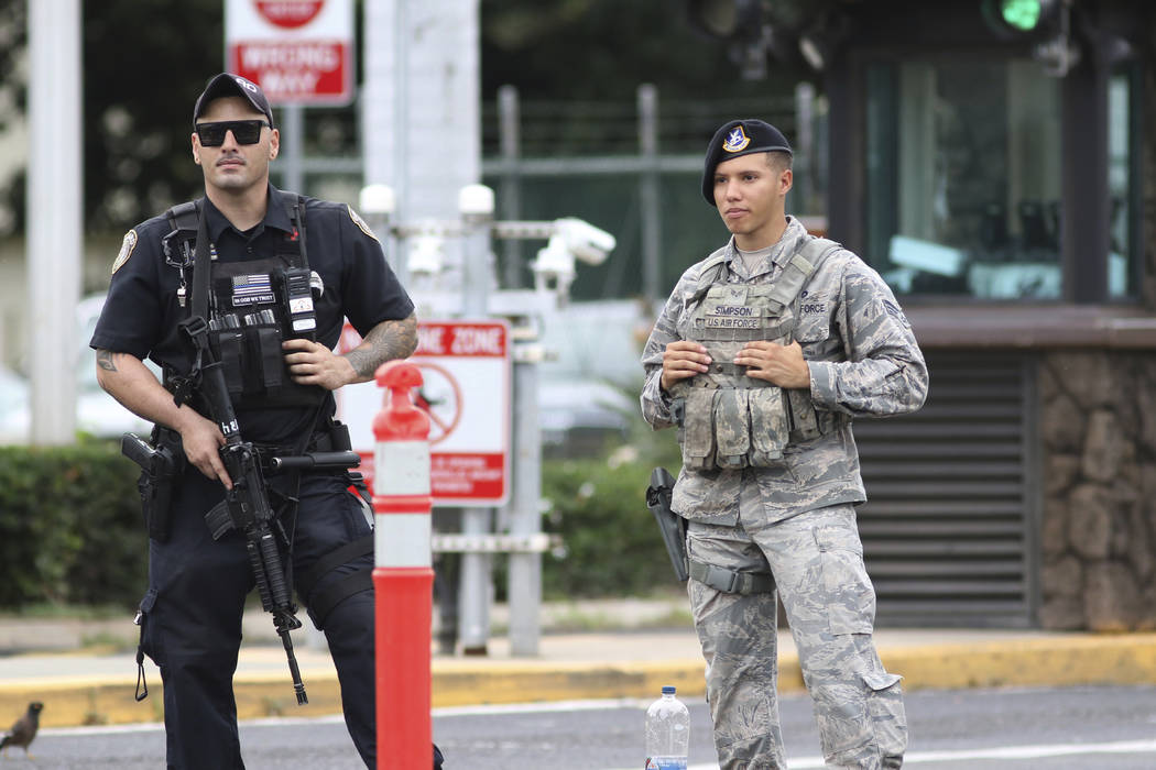 Security stands guard outside the main gate at Joint Base Pearl Harbor-Hickam, in Hawaii, Wedne ...