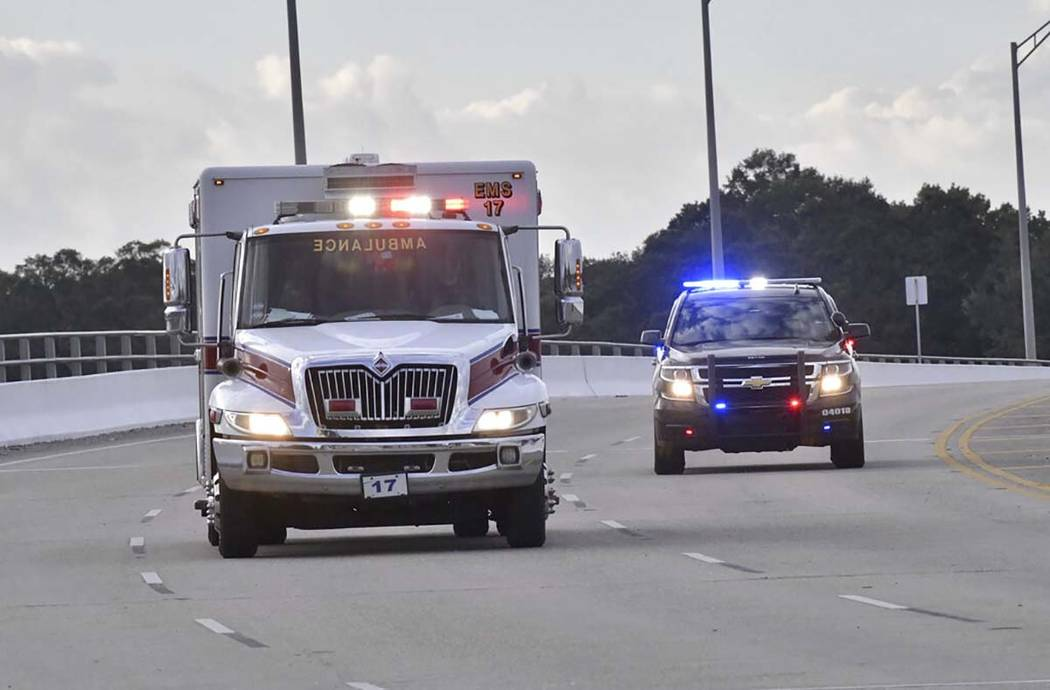 Police cars escort an ambulance after a shooter open fire inside the Pensacola Air Base, Friday ...