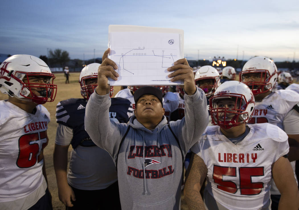 Liberty High School coach Al Tucay holds up a play for the team during football practice at Lib ...