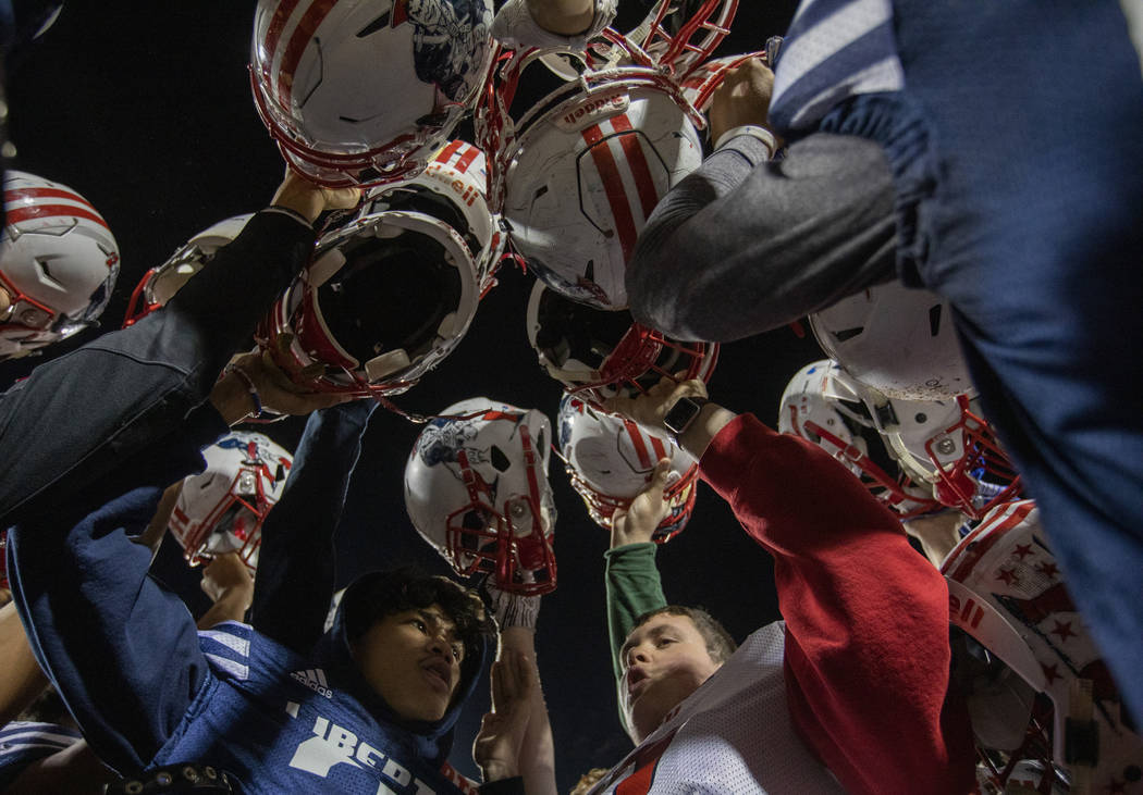 Senior members of the football team bring their helmets together at the end of practice at Libe ...