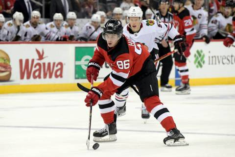 New Jersey Devils center Jack Hughes (86) skates with the puck as he is pursued by Chicago Blac ...