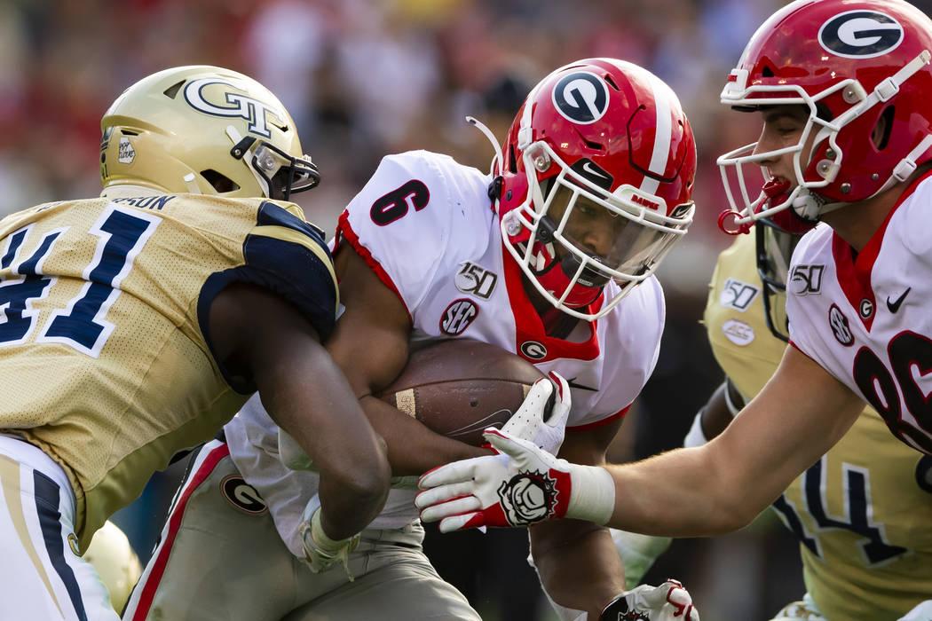 Georgia running back Kenny McIntosh runs with Georgia Tech defensive lineman Jaquan Henderson ( ...