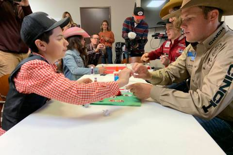 Angelo Mayorga, left, and Wrangler NFR tie-down roper Caleb Smidt work together on a project Fr ...
