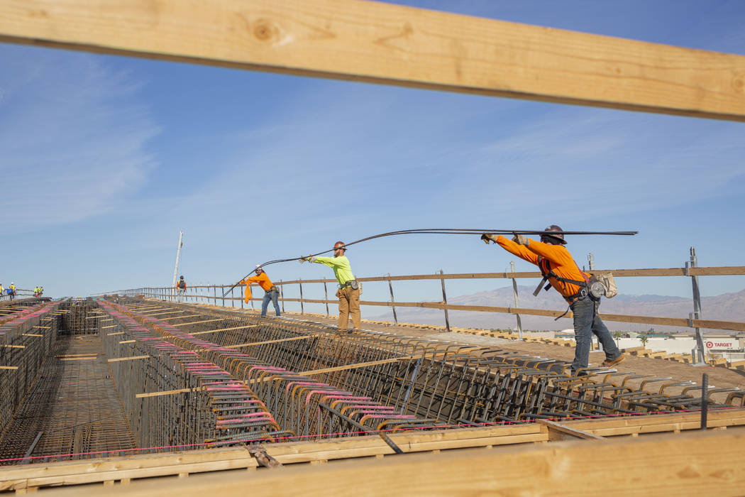 Steel workers put in rods during construction on the Centennial Bridge linking the eastbound 21 ...