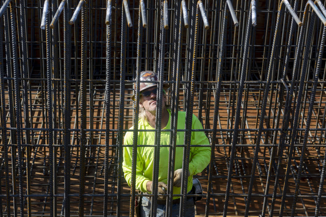 Steel worker Scott McBride puts in rods during construction on the Centennial Bridge linking th ...