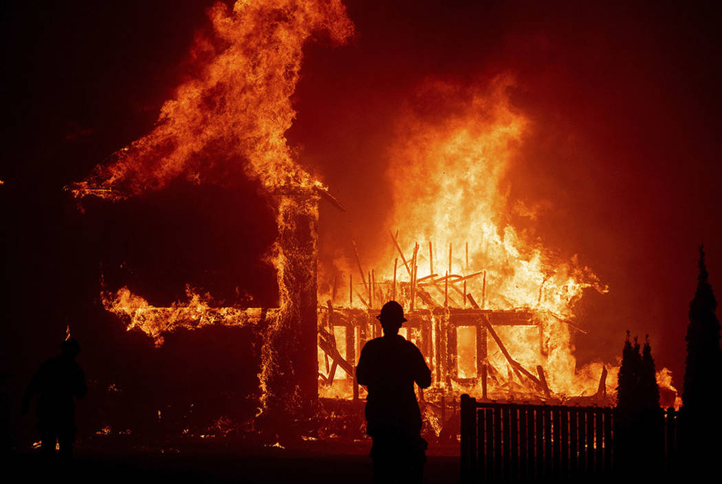 A home burns as a wildfire called the Camp Fire rages through Paradise, Calif., in November 201 ...