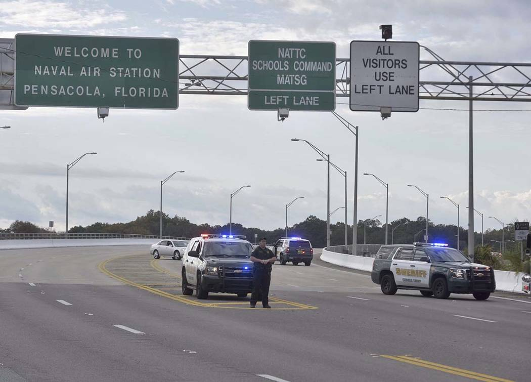 Police vehicles block the entrance to the Pensacola Air Base, Friday, Dec. 6, 2019 in Pensacola ...