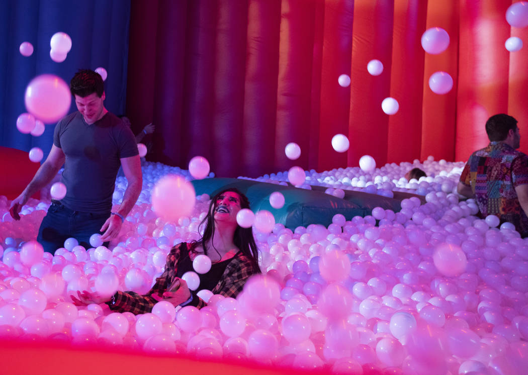 Rosa Garcia of Las Vegas, center, throws plastic balls into the air in the ball pit at Intersec ...