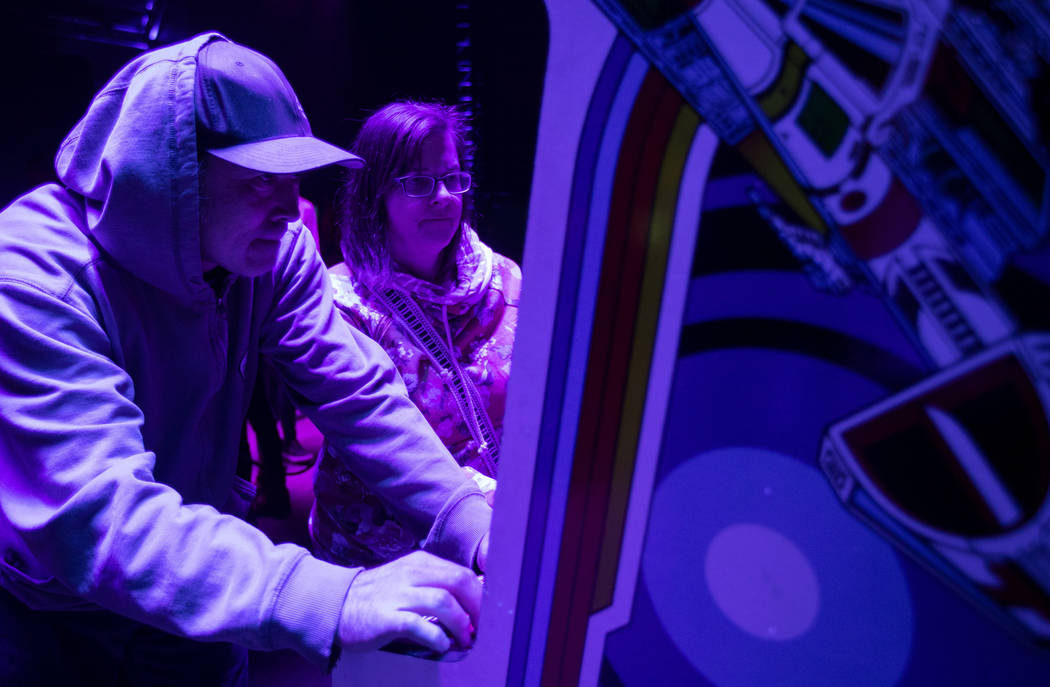 Derek McCaughey, left and Sarah Holeton, right, play a game in the arcade at Intersect Festival ...