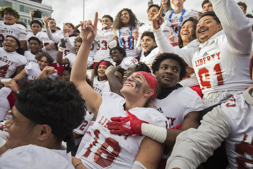 Liberty junior quarterback Daniel Britt (18) points to the sky as he celebrates with teammates ...