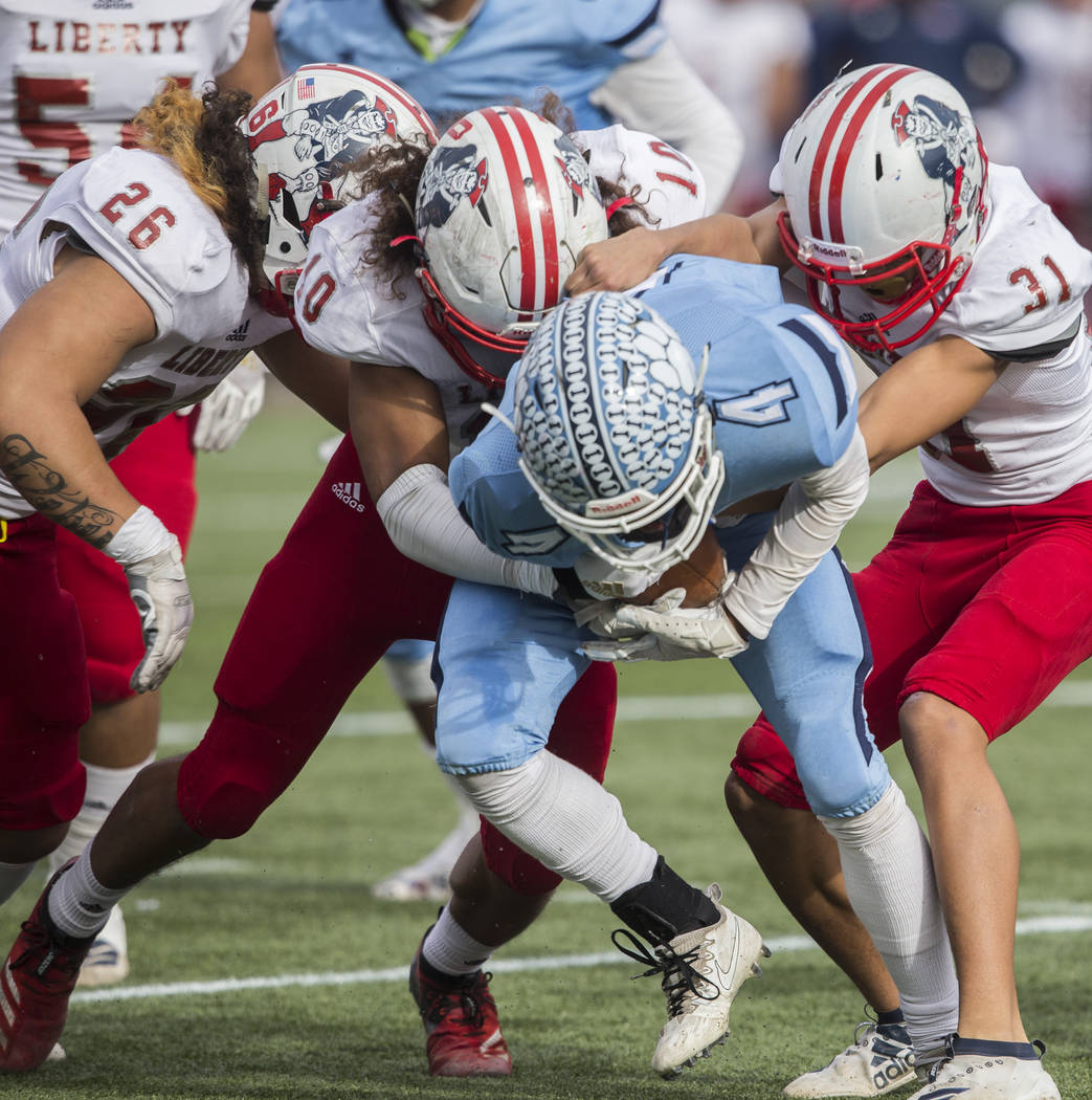 Centennial senior Aaron Johnson (4) is wrapped up in the backfield by Liberty sophomore linebac ...