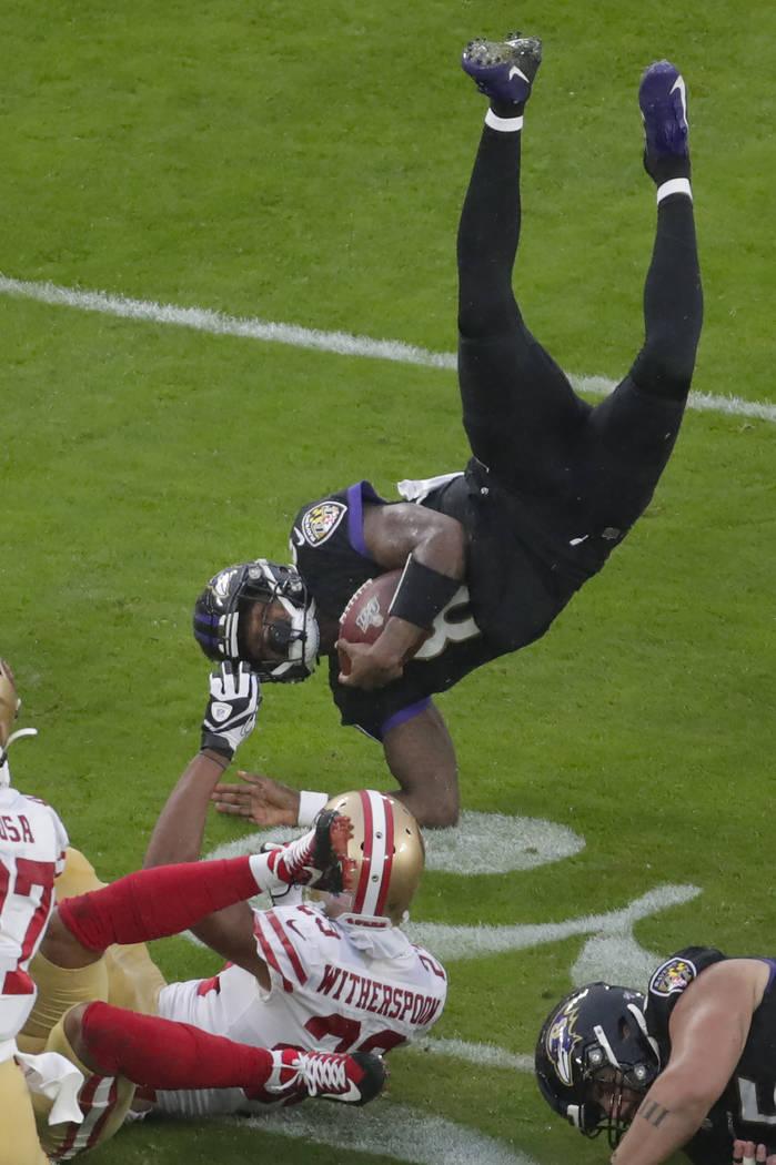 Baltimore Ravens quarterback Lamar Jackson (8) flips after being tripped by San Francisco 49ers ...
