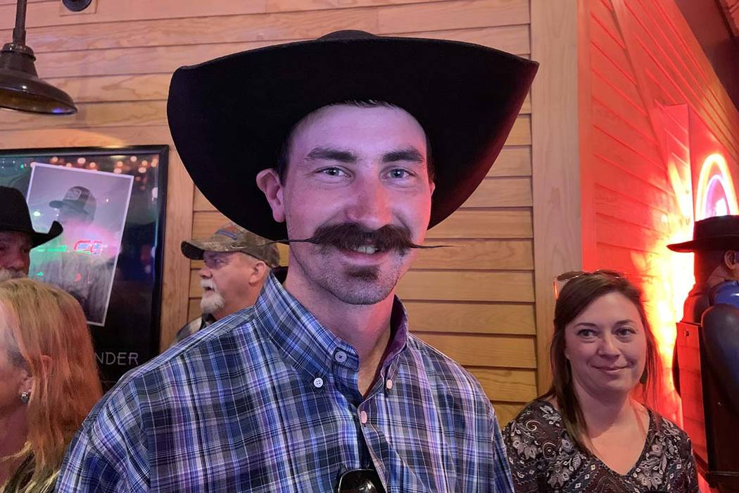Ryder Young of Boise, Idaho, shows off his handlebar mustache while waiting among those in a lo ...