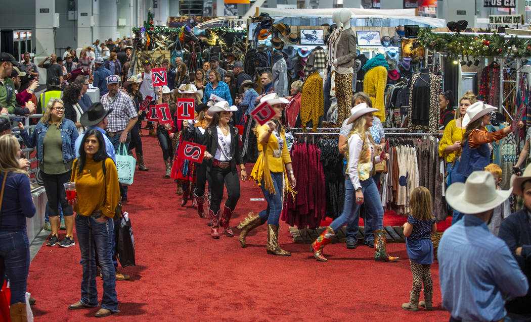 Contestants walk past the crowd in the Miss Rodeo America Justin Boot Parade during Cowboy Chri ...