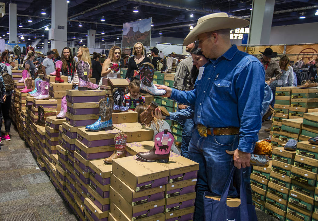 Shoppers check out the variety of Roper Boots for sale during Cowboy Christmas at the Las Vegas ...
