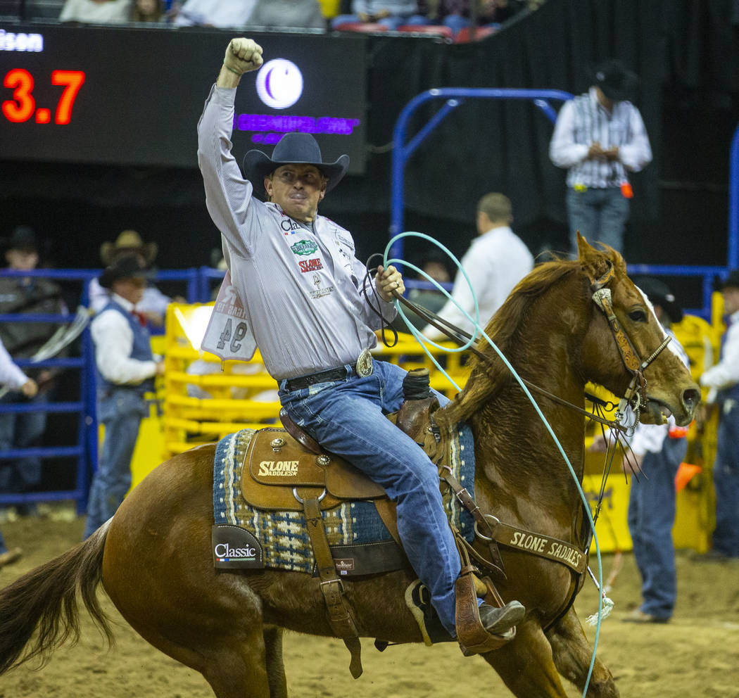 Heeler Cole Davison of Stephenville, Texas, celebrates a winning time in Team Roping with heade ...