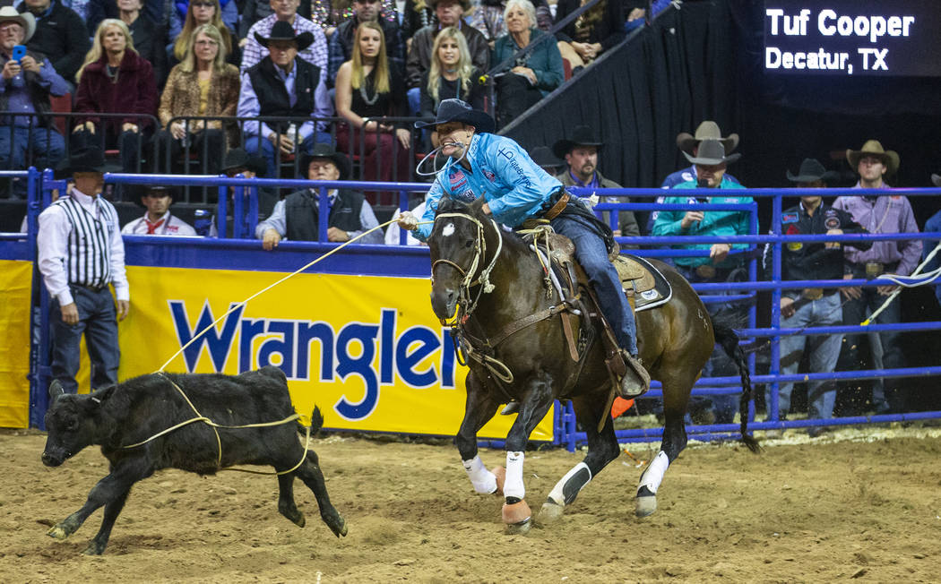 Tuf Cooper of Decatur, Texas, ropes a steer while taking first place in Tie-Down Roping with a ...