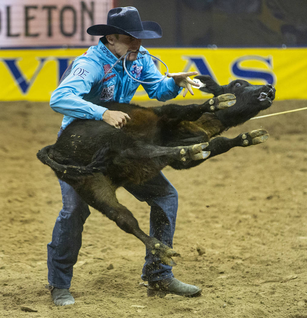 Tuf Cooper of Decatur, Texas, tosses a steer while taking first place in Tie-Down Roping with a ...