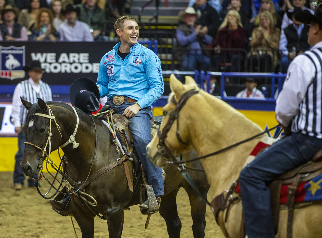 Tuf Cooper of Decatur, Texas, celebrates taking first place in Tie-Down Roping with a time of 6 ...