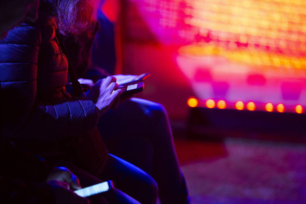 Festival-goers use their cell phones in one of the lounge areas as music plays on the stages on ...