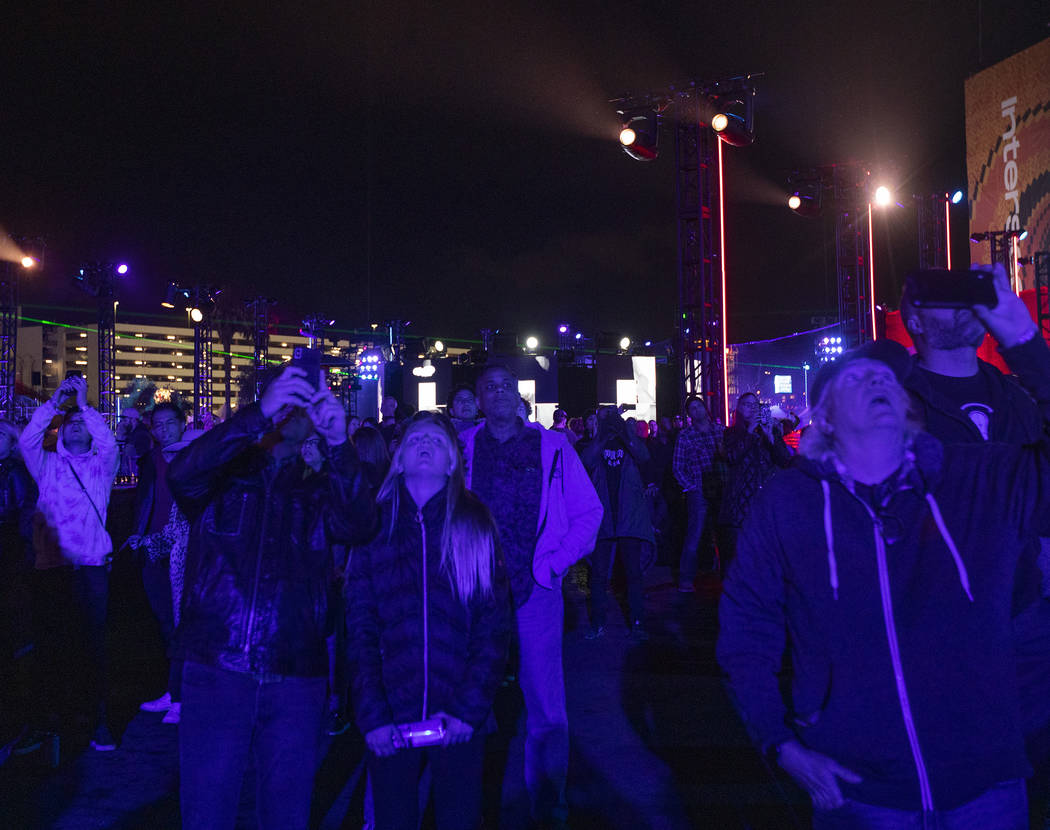 Festival-goers look up at The Expanse Drone Space Opera performance on Saturday, Dec. 7, 2019, ...