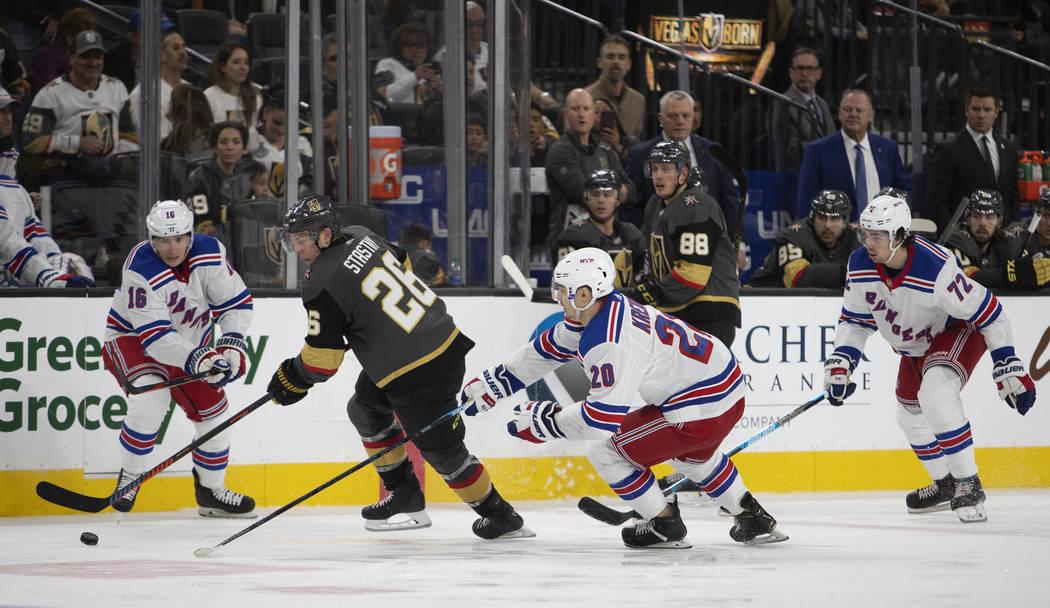 Golden Knights center Paul Stastny (26) goes for the puck alongside New York Rangers center Rya ...