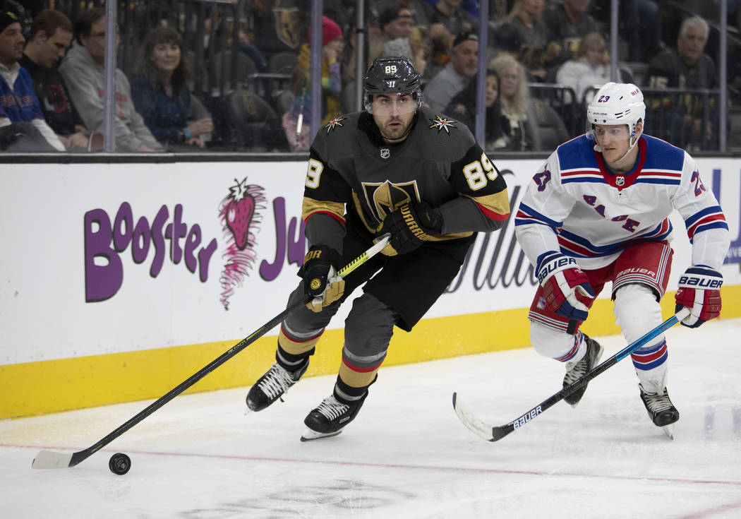 Golden Knights right wing Alex Tuch (89) looks to pass the puck next to New York Rangers defens ...