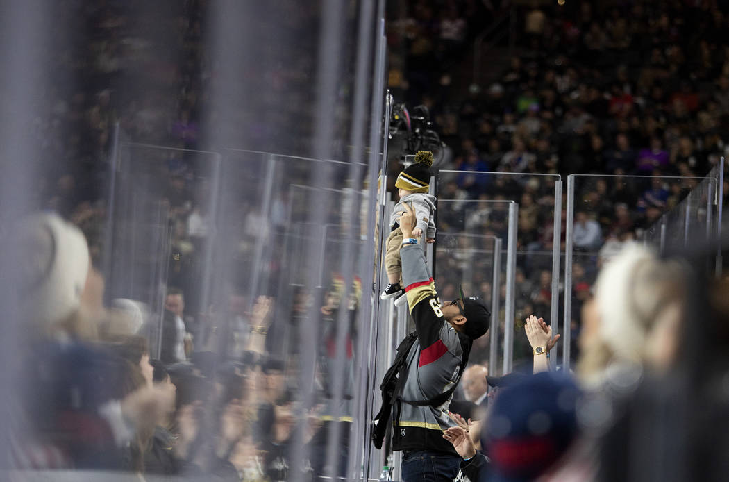 A Golden Knights fan holds up their baby during the third period of the game against the New Yo ...