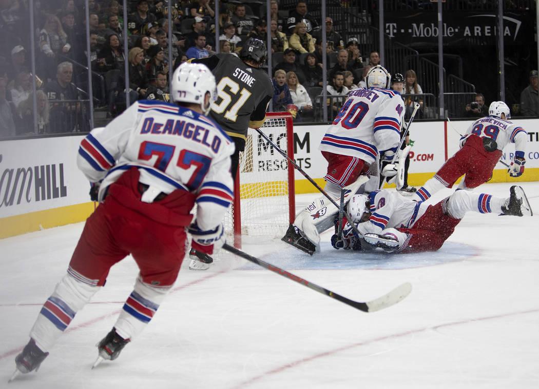 New York Rangers defenseman Jacob Trouba (8) slides into New York Rangers goaltender Alexandar ...