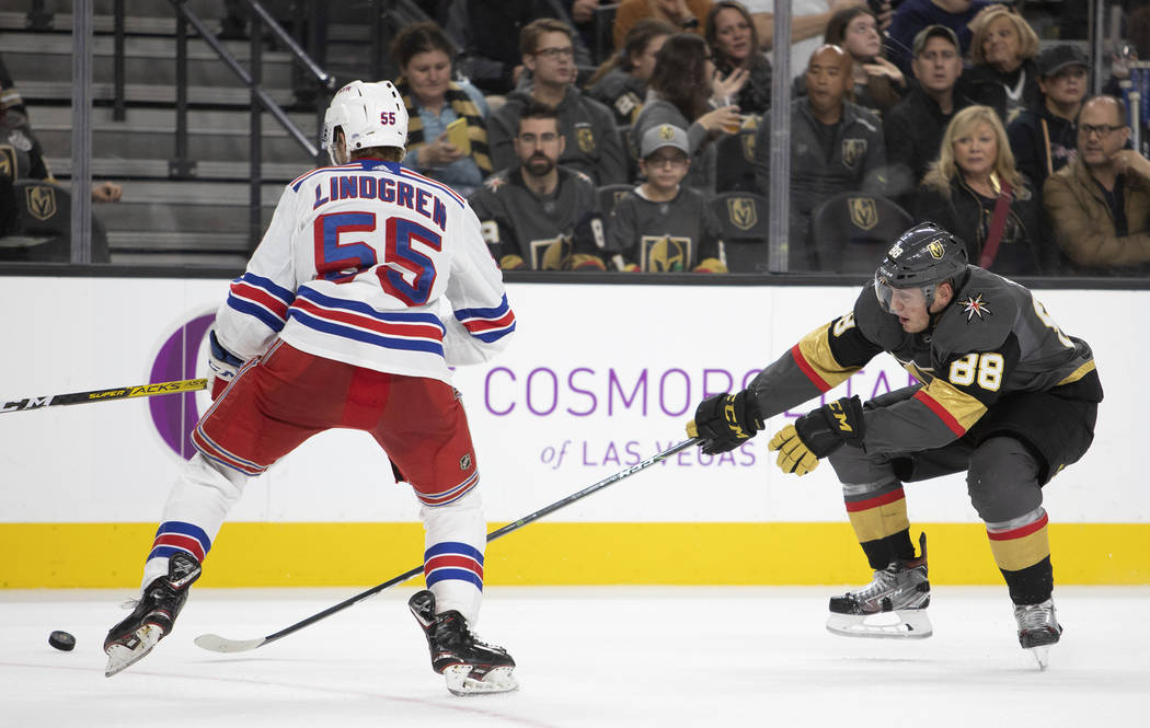 Golden Knights defenseman Nate Schmidt (88) reaches to take control of the puck as New York Ran ...